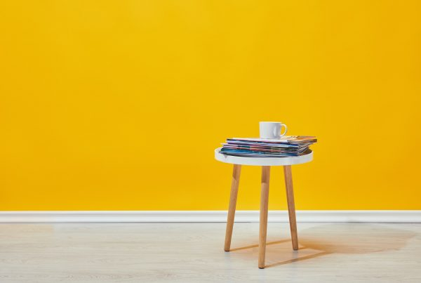 Little wooden table with pile of magazines and white cup of coffee near yellow wall